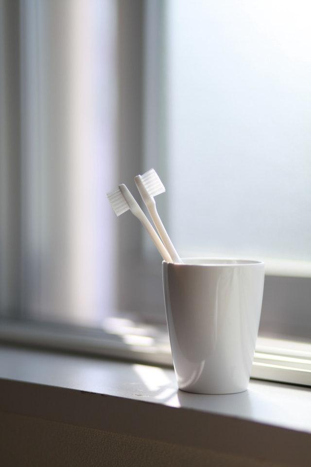 2 białe szczoteczki do zębów wsadzone do białego kubka przy oknie na parapecie